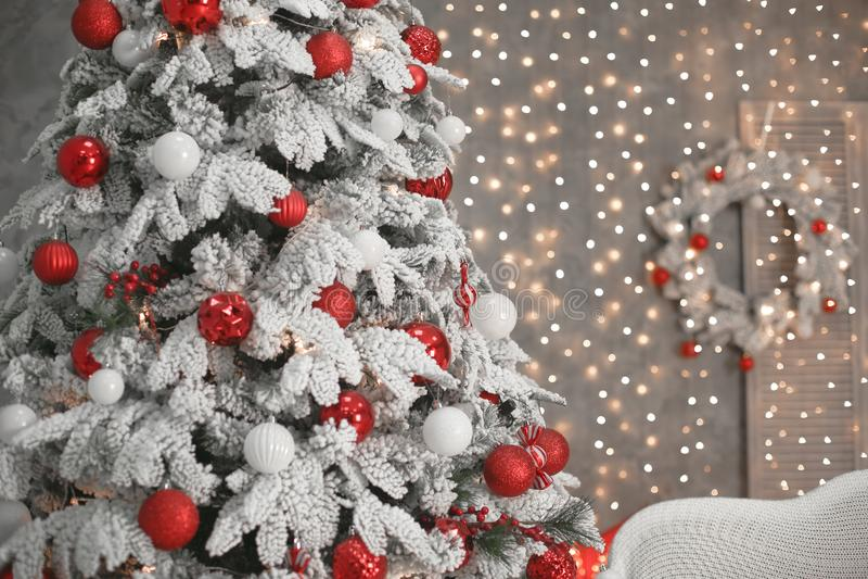 Árbol de navidad Nevado con los regalos rojos antes de luces y del wrea del bokeh fotos de archivo