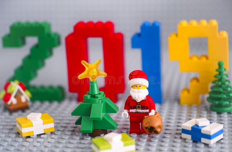 Árbol de Navidad, Santa Cláusula con bolso y regalos contra los números 2019 hechos por bloques de Lego en placas grises foto de archivo