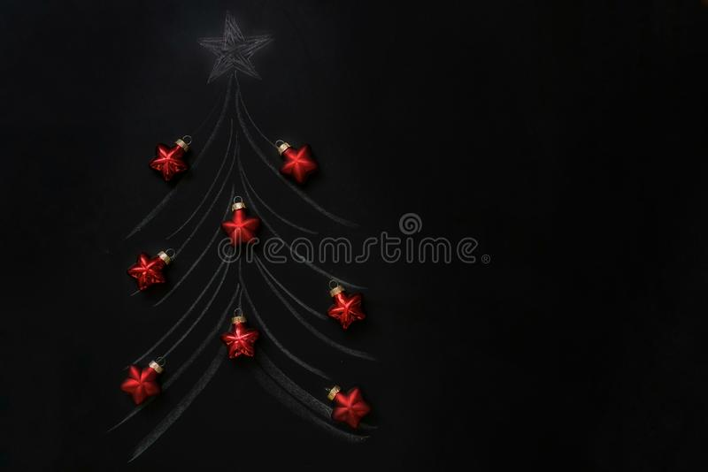 árbol de navidad tiza-dibujado en una pizarra con las bolas rojas reales de la Navidad y la inscripción tiza-escrita Feliz Navida foto de archivo libre de regalías