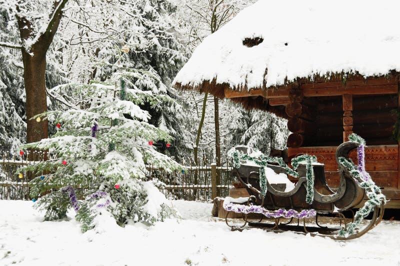 Árbol de navidad vestido, cabaña de madera vieja y trineo de Santa Claus en un bosque tranquilo del invierno foto de archivo