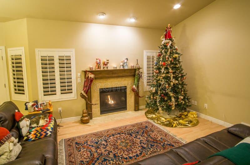 Árbol de navidad y chimenea hermosos con el gato que se relaja en el sofá imágenes de archivo libres de regalías