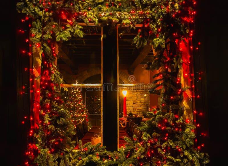 Árbol de navidad y chimenea vistos a través de una ventana de cabina de madera fotografía de archivo