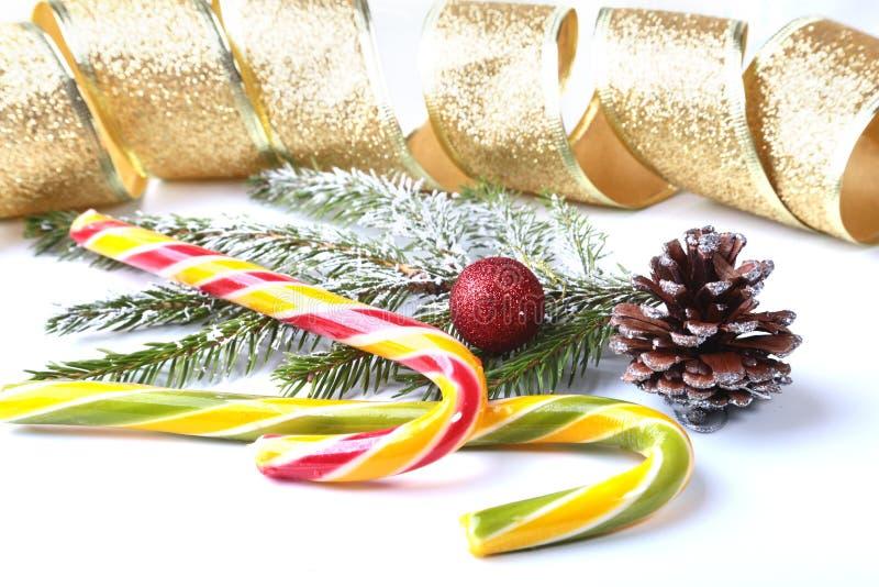 Árbol de navidad y conos, las bolas coloridas del Año Nuevo con la caja de la cinta, del lollypop y de regalo en el fondo blanco  imagenes de archivo