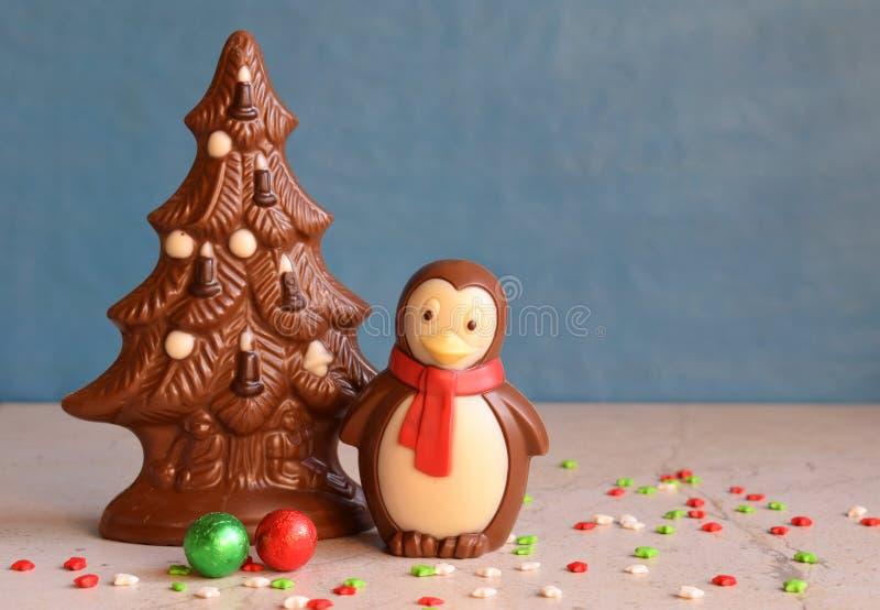 Árbol de navidad y pingüino del chocolate en fondo azul Feliz Año Nuevo y concepto de la Feliz Navidad Copie el espacio fotos de archivo