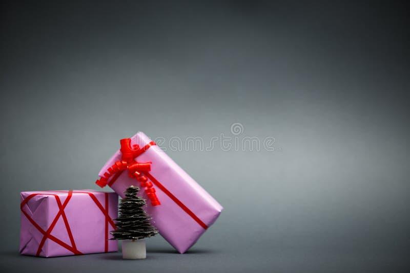 Árbol de navidad y regalos de papel en fondo gris imagen de archivo