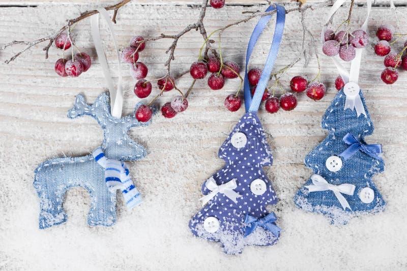 Árbol de navidad y reno en una rama con las bayas foto de archivo