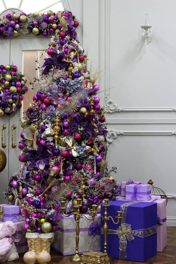 Árbol de oro de la libélula de la Navidad con las decoraciones y los regalos coloridos en el interior decorativo para el día de f foto de archivo