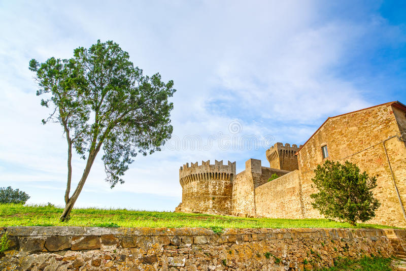 Árbol en señal del pueblo de Populonia, paredes de la ciudad y torre medievales en fondo. Toscana, Italia. fotografía de archivo