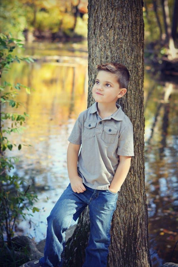 Árbol que hace una pausa del muchacho que mira para arriba foto de archivo