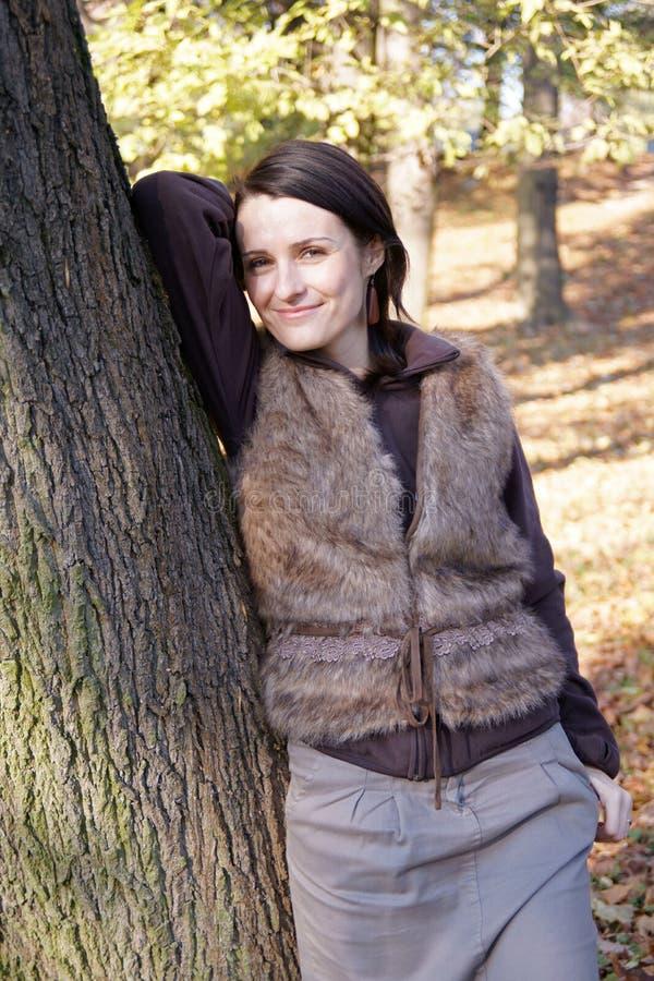 Árbol que se inclina de la mujer del otoño imagen de archivo