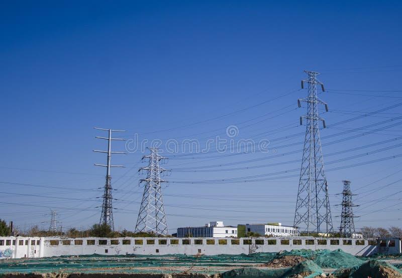 Árbol y líneas de alto voltaje y torres en emplazamiento de la obra foto de archivo libre de regalías