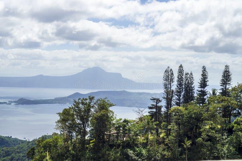Árboles en el lago y el volcán de desatención hilltop imagen de archivo