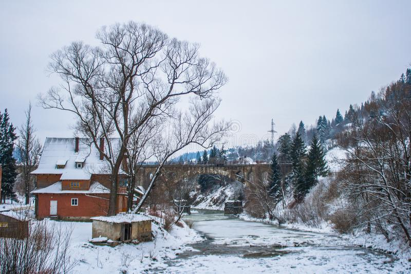 Árboles Nevado del camino nevoso y del bosque del invierno wallpaper Puente y casa viejos fotografía de archivo