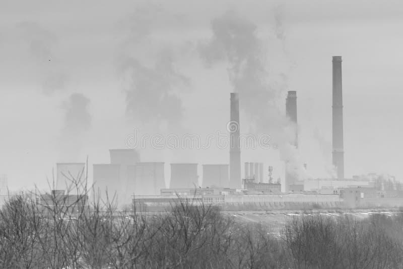 Árboles secos congelados en invierno y hornos industriales negro y wh fotografía de archivo libre de regalías