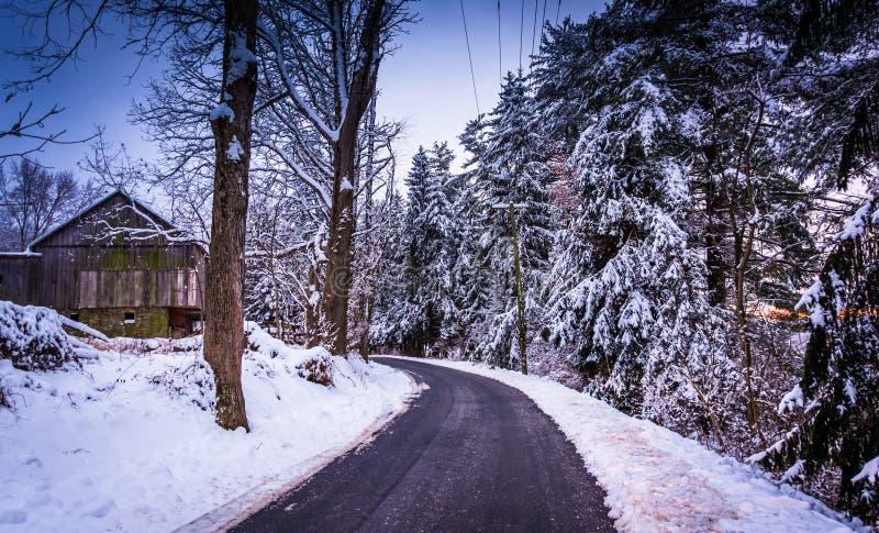 Árboles y granero nevados de pino a lo largo de una carretera nacional en C rural foto de archivo