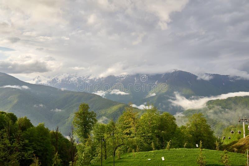 Árboles y teleférico verdes en el fondo de altas montañas nevosas Día de primavera nublado en las montañas fotos de archivo libres de regalías