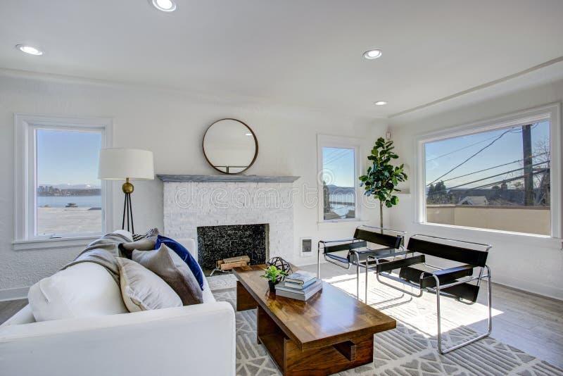 Área blanca de la sala de estar con la tabla de cóctel de la chimenea y de madera imagenes de archivo