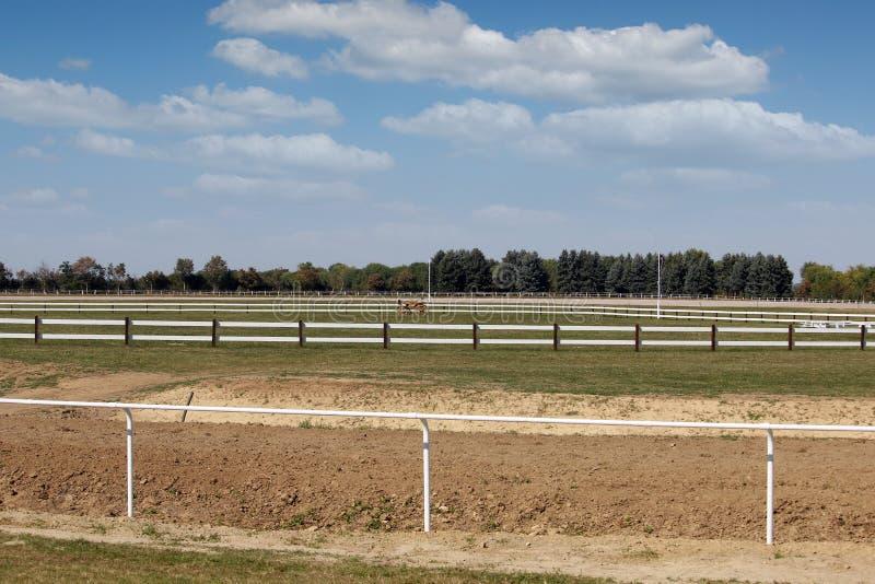Área da corrida de cavalos do hipódromo com grama verde e as cercas brancas imagens de stock