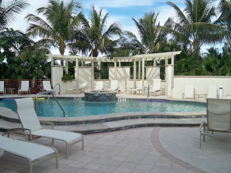 Área da piscina bonita com palmeiras e cadeiras de sala de estar imagem de stock