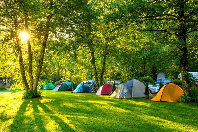 Área de acampamento das barracas, amanhecer com luz do sol imagens de stock royalty free