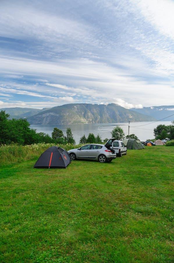 Área de acampamento perto do fiorde com carros e barracas na grama imagem de stock royalty free