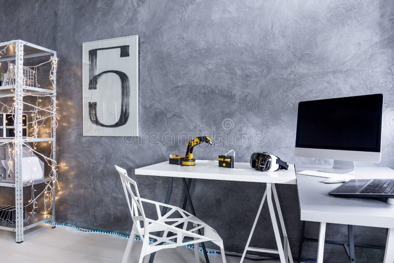 Área de estudio gris moderna con un escritorio grande imagen de archivo