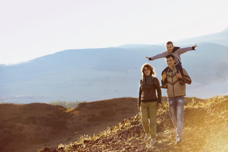 Área de montañas de la naturaleza de la familia que camina feliz imagen de archivo