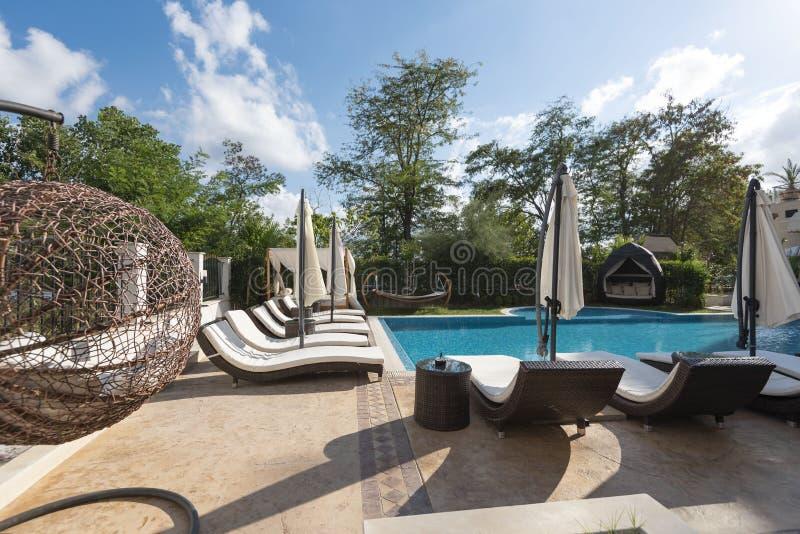 Área de piscina com as camas brancas do sol F?rias de ver?o imagem de stock