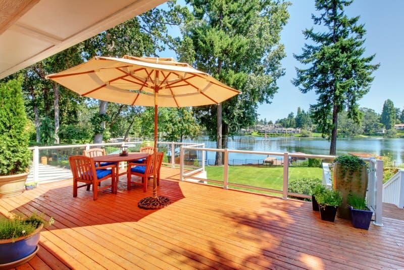 Área del salón en cubierta defendida de la huelga con la tabla, el paraguas y las sillas de patio fotos de archivo libres de regalías