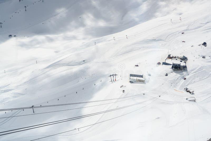 Área do esqui na neve na geleira do zugspitze com elevador, teleférico e inclinações nos cumes entre Alemanha e Áustria pró fotografia de stock