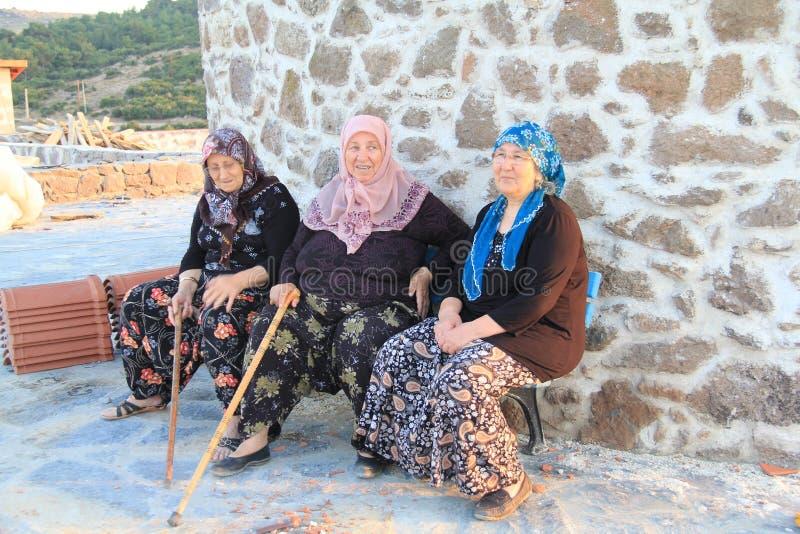 Área egeia - mulheres idosas do aldeão que sentam-se no moinho de vento fotos de stock royalty free