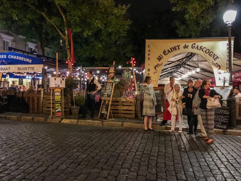 Área exterior do café da parte externa da pausa dos jantares da noite, Lugar du Tertre, Paris, França imagem de stock