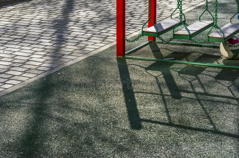 ?rea exterior do campo de jogos das crian?as, passagem pavimentada no parque em uma tarde da mola com sombras longas foto de stock royalty free
