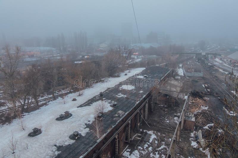 ?rea industrial abandonada en niebla Silueta del hombre de negocios Cowering foto de archivo libre de regalías