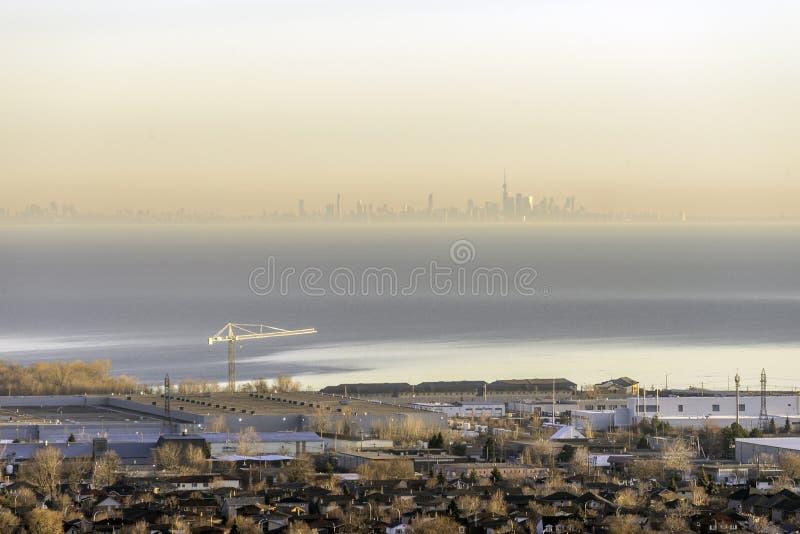 Área industrial, grúa y casas brillando en la salida del sol con T nebuloso foto de archivo