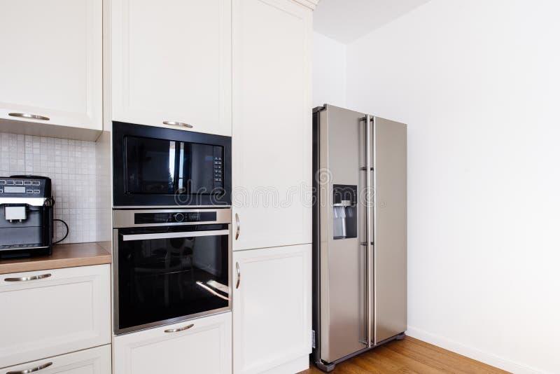 Área moderna da cozinha, assoalho de madeira com refrigerador moderno e dispositivos imagem de stock
