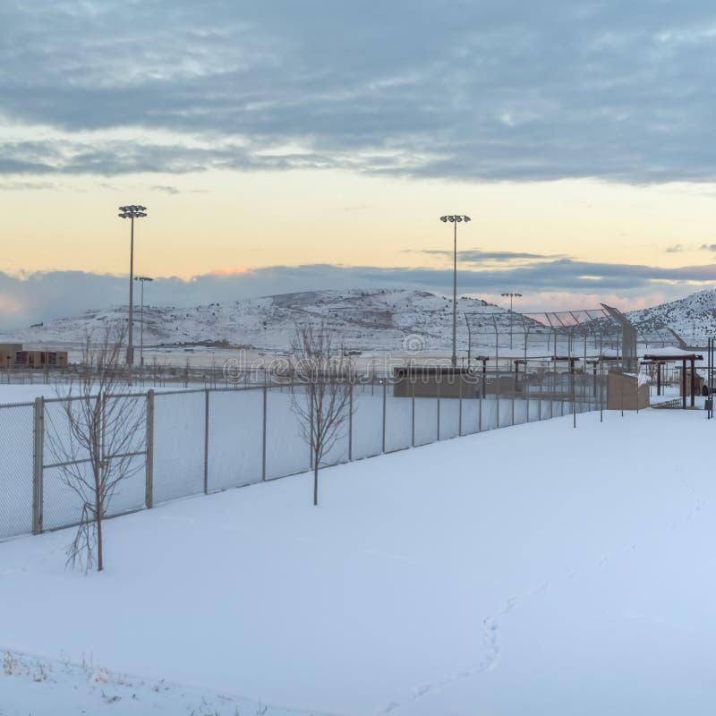 Área nevada del marco cuadrado dentro de una cerca con los proyectores altos en el perímetro imagen de archivo