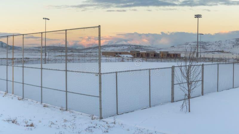 Área nevada del marco del panorama dentro de una cerca con los proyectores altos en el perímetro imagen de archivo libre de regalías
