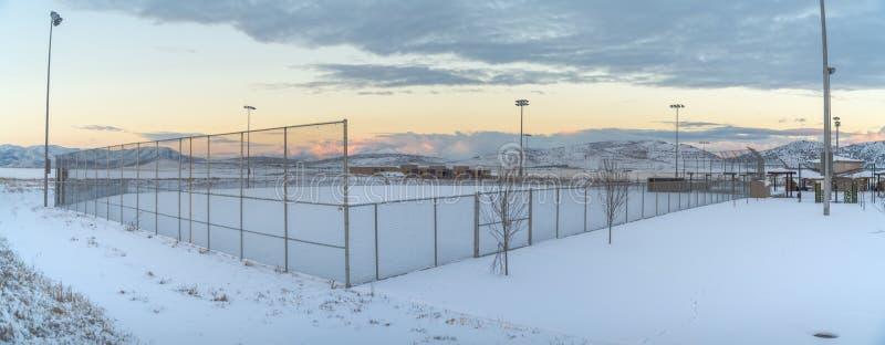 Área nevada dentro de una cerca con los proyectores altos en el perímetro imagen de archivo
