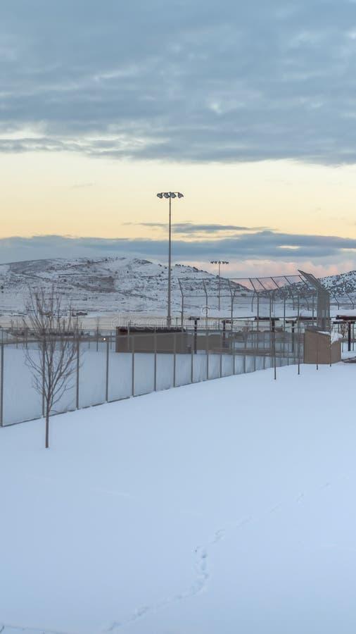 Área nevada vertical dentro de una cerca con los proyectores altos en el perímetro fotografía de archivo