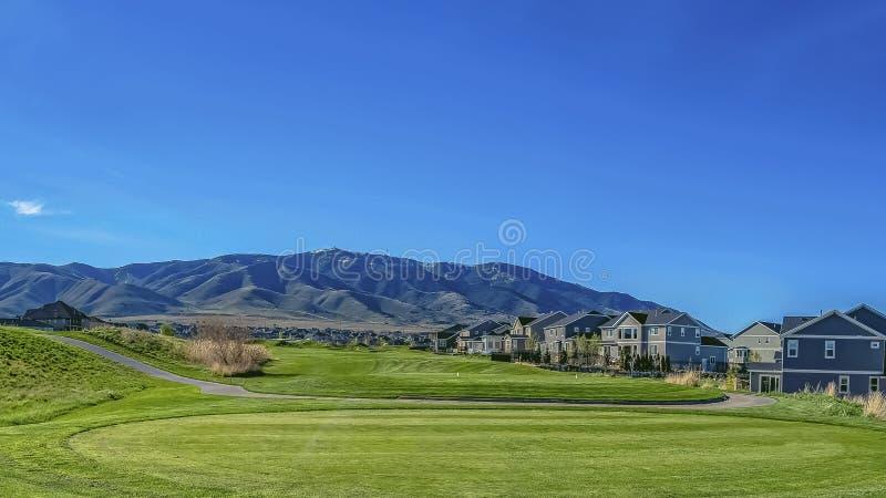 Área residencial do quadro do panorama em um vale com vista da montanha sob o céu azul e o sol brilhante imagens de stock