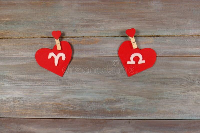 Áries e escalas sinais do zodíaco e do coração Backgrou de madeira imagens de stock royalty free