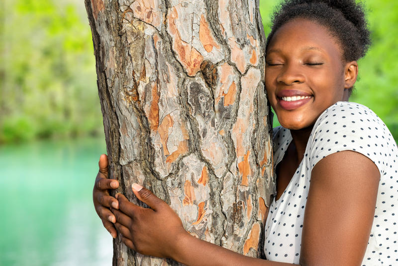 Árvore africana do abraço da menina nas madeiras fotografia de stock royalty free