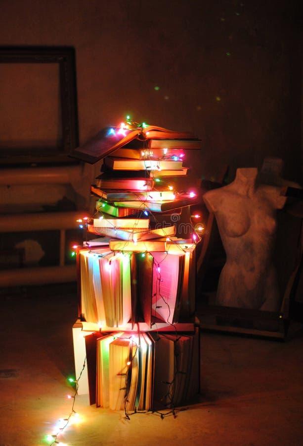 Árvore alternativa criativa dos livros e de festões coloridas Luzes de Natal Manequins, quadros no fundo imagem de stock