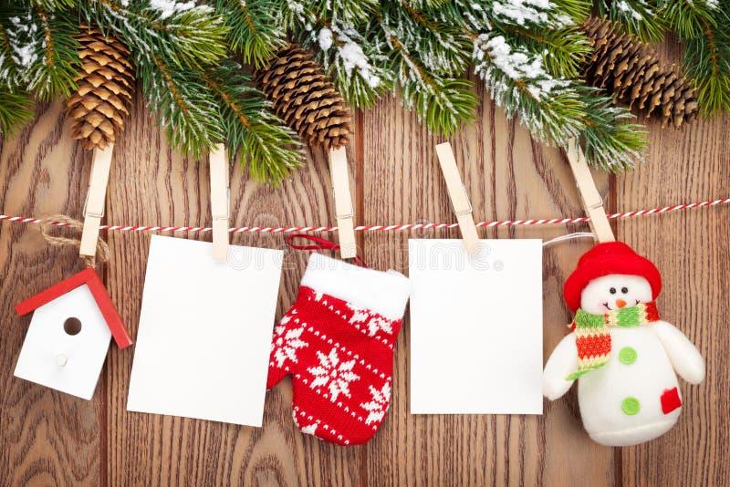 Árvore de abeto da neve, quadros da foto e decoração do Natal na corda sobre rus imagem de stock royalty free