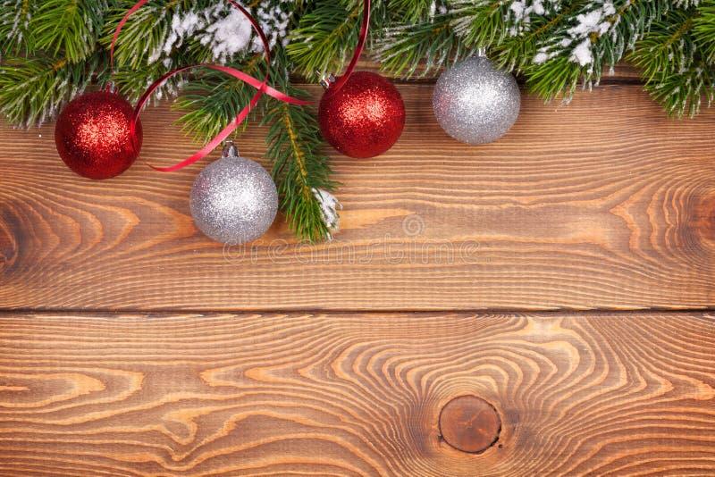 Árvore de abeto do Natal com neve e quinquilharias na placa de madeira rústica foto de stock