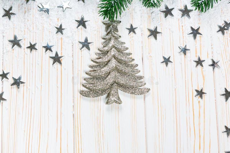 Árvore de abeto do Natal na neve com as estrelas de prata no fundo de madeira branco fotos de stock
