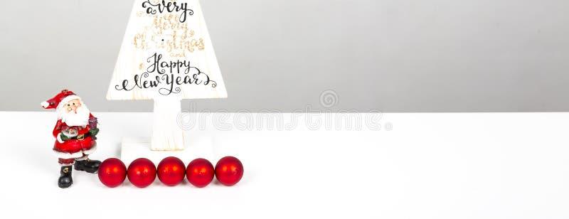 Árvore de madeira do Natal mínimo bonito com Christmass alegre e o ano novo feliz escritos, com Santa Claus pequena, no backgound imagens de stock
