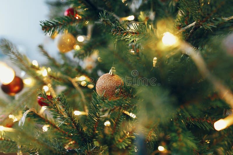 Árvore de Natal à moda com luzes da festão e dourado bonitos fotografia de stock royalty free
