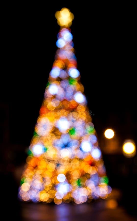 Árvore de Natal de Bokeh com iluminações coloridas foto de stock